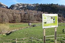 Explanada delante del refugio, con un panel explicativo y con el Paso del Salto del Caballo al fondo.