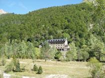 Al otro lado destaca un frondoso bosque y el edificio del Parador del Monte Perdido.