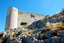 Torre circular suroeste y muralla del castillo del Montgrí. Se aprecian las almenas, las aspilleras y el matacán.