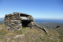 Justo al lado de las antenas hay una cabaña de piedra seca.