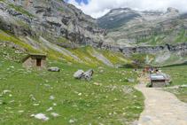 Cabaña de pastores, panel explicativo y, al fondo, la cabecera del valle.
