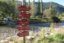 Señalización vertical con banderolas junto al río, eje vertebrador del valle.