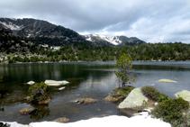Lago de Malniu rodeado de árboles y de las montañas ceretanas.