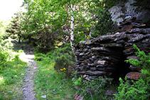 Cabaña de piedra seca dentro del bosque.