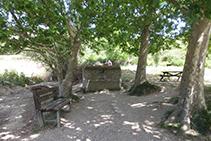 Zona con bancos, mesas y una fuente.