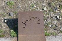Placa de acero corten que hay en el borde del camino: S´Àliga dibujada.