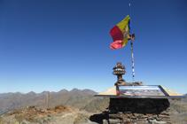Cima del Comapedrosa con una mesa de orientación y la bandera andorrana. El macizo de la Pica d´Estats al fondo.
