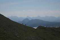 Dos excursionistas subiendo hacia la cima. Al fondo: la Mesa de los Tres Reyes, el Petrechema, el Sobarcal, el Acherito y el Chinebral de Gamueta.