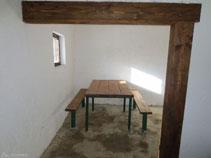 Mesa y bancos dentro del refugio