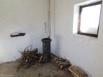 Interior del refugio Oller con una estufa de leña