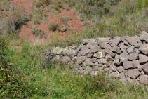 Murete de piedras con la señal amarilla del sendero que debemos tomar.