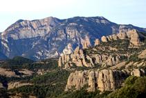 En primer término vemos las rocas montserratinas de la sierra de los Obacs. En segundo término tenemos la salvaje sierra de Aubenç, con el Coscollet despuntando por encima de los abismos. Intuimos el corte que hace el río Segre entre las dos sierras.