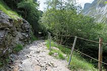 Tramo rocoso estrecho en el que una barandilla separa el límite del camino del acantilado que cae hasta la Neste de la Géla.