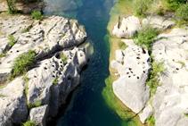La erosión de las aguas sobre el lecho del río.